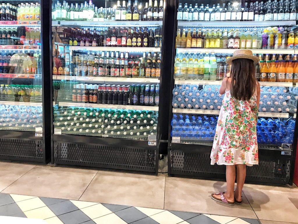 Bambina con cappello che osserva le bibite nel frigo in Autogrill
