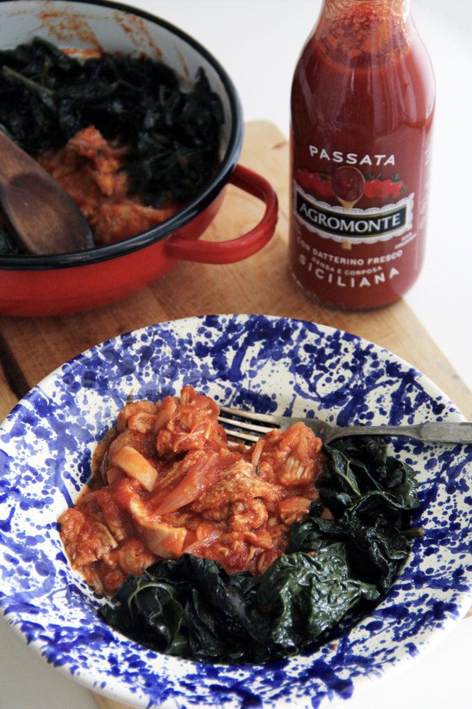 Trippa al pomodoro nel piatto e nella pentola con bottiglia di salsa