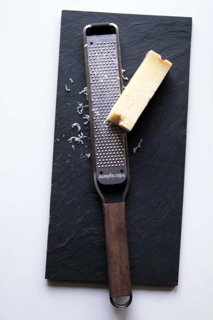 Microplane Master Zester poggiata su tavola in ardesia con formaggio