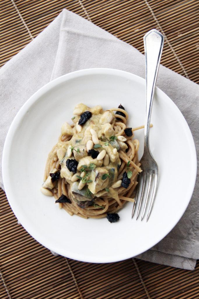Spaghetti integrali con sgombro, prugne, porri e pinoli fotografati dall'alto con forchetta