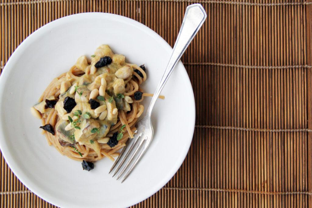 Spaghetti integrali con sgombro, prugne, porri e pinoli su tovaglietta in bambù