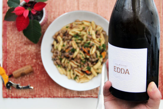 Edda bianco Salento IGP in primo piano con piatto di caratelli fagioli e cozze