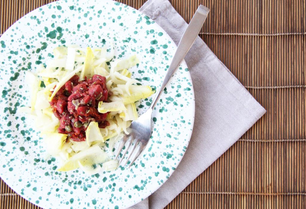 Tartare di cavallo con indivia su piatto colorato di Grottaglie e forchetta.