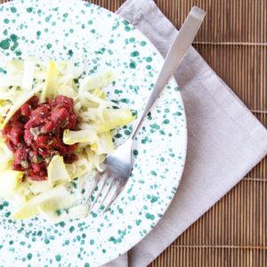 Tartare di cavallo su insalata con tovagliolo e forchetta