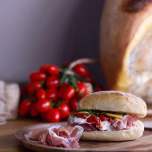 Panino con Prosciutto Crudo di San Daniele DOP e sullo sfondo prosciutto e pomodorini