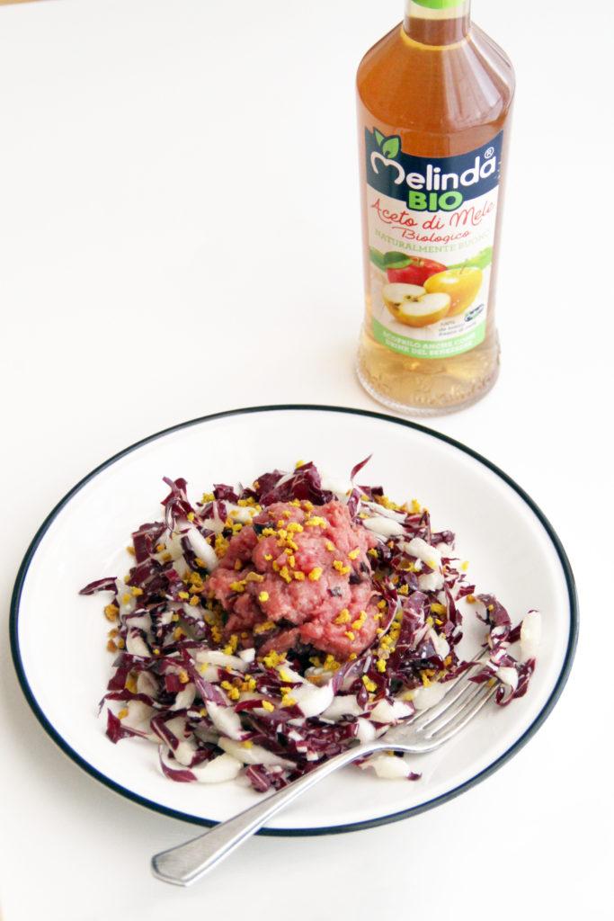 artare nel piatto su tavolo bianco per Aceto Melinda Bio e bottiglia in foto