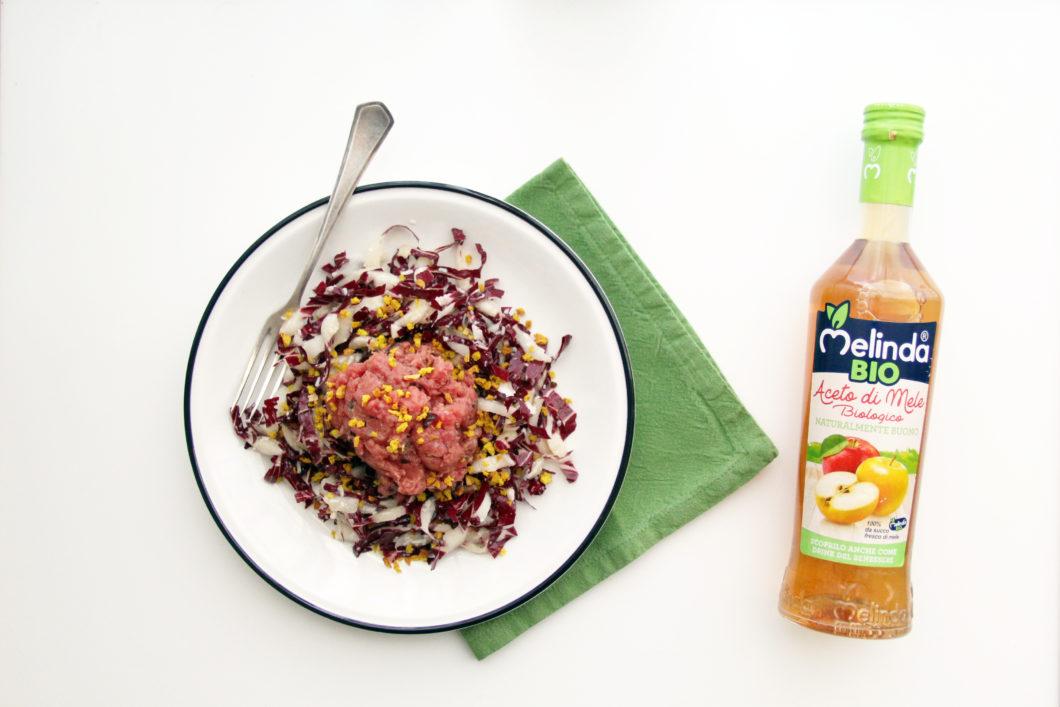 Tartare su insalata di radicchio con granella per Aceto di mele Melinda con tovagliolo verde e forchetta