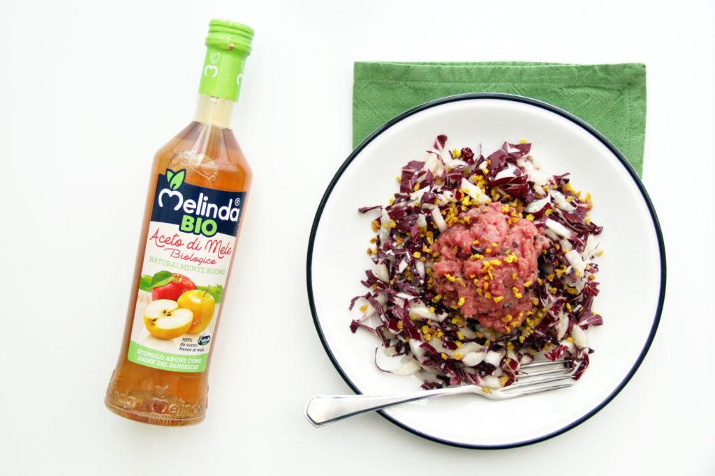 Tartare su insalata di radicchio con granella per Aceto di mele Melinda sulla sinistra con tovagliolo verde
