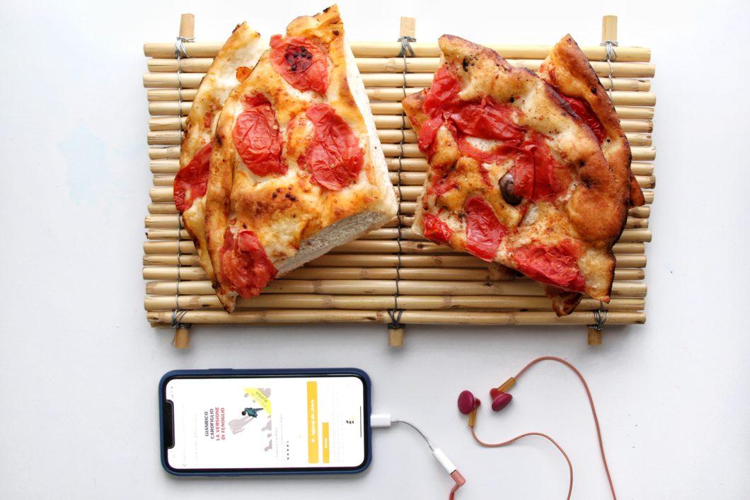 Immagine di uno smartphone con Audible e cuffiette e accanto Focaccia Barese