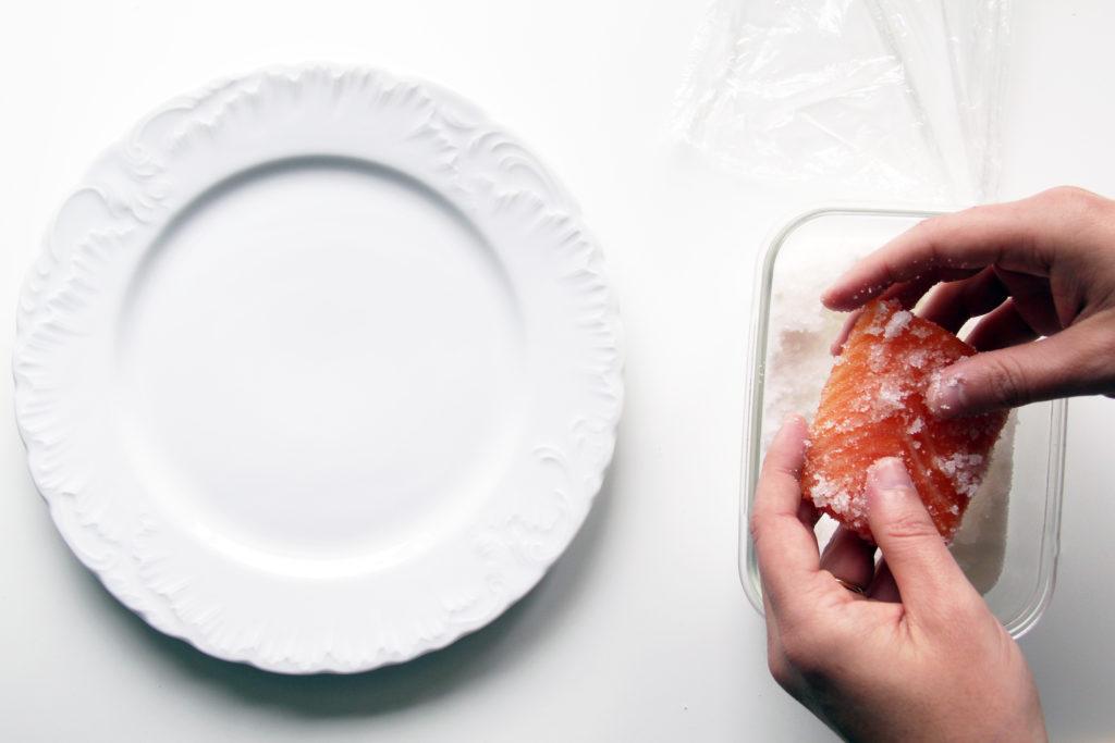 Salmone sotto sale e zucchero di canna mentre viene tirato fuori