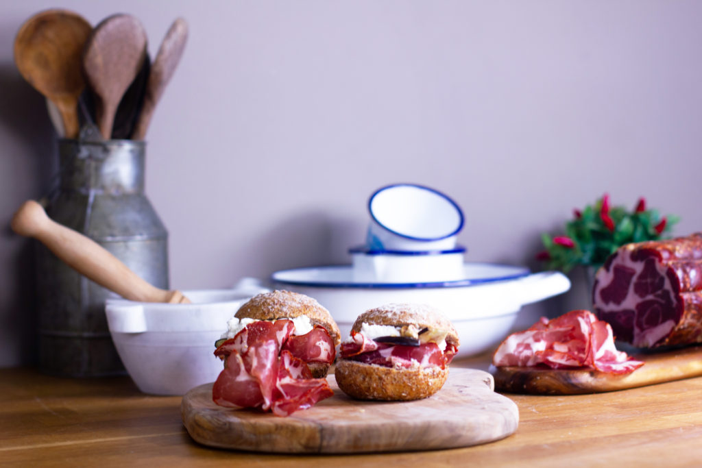 Due panini con capocollo di Calabria DOP poggiati su un tagliere