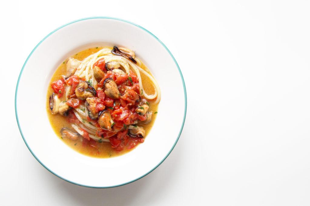 Spaghetti con le cozze su tavolo bianco