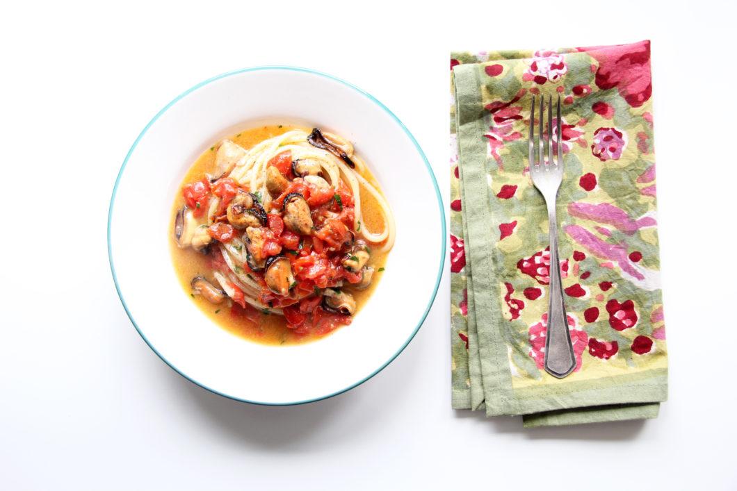 Spaghetti con le cozze con forchetta e tovagliolo colorato con fiori e forchetta poggiata sopra