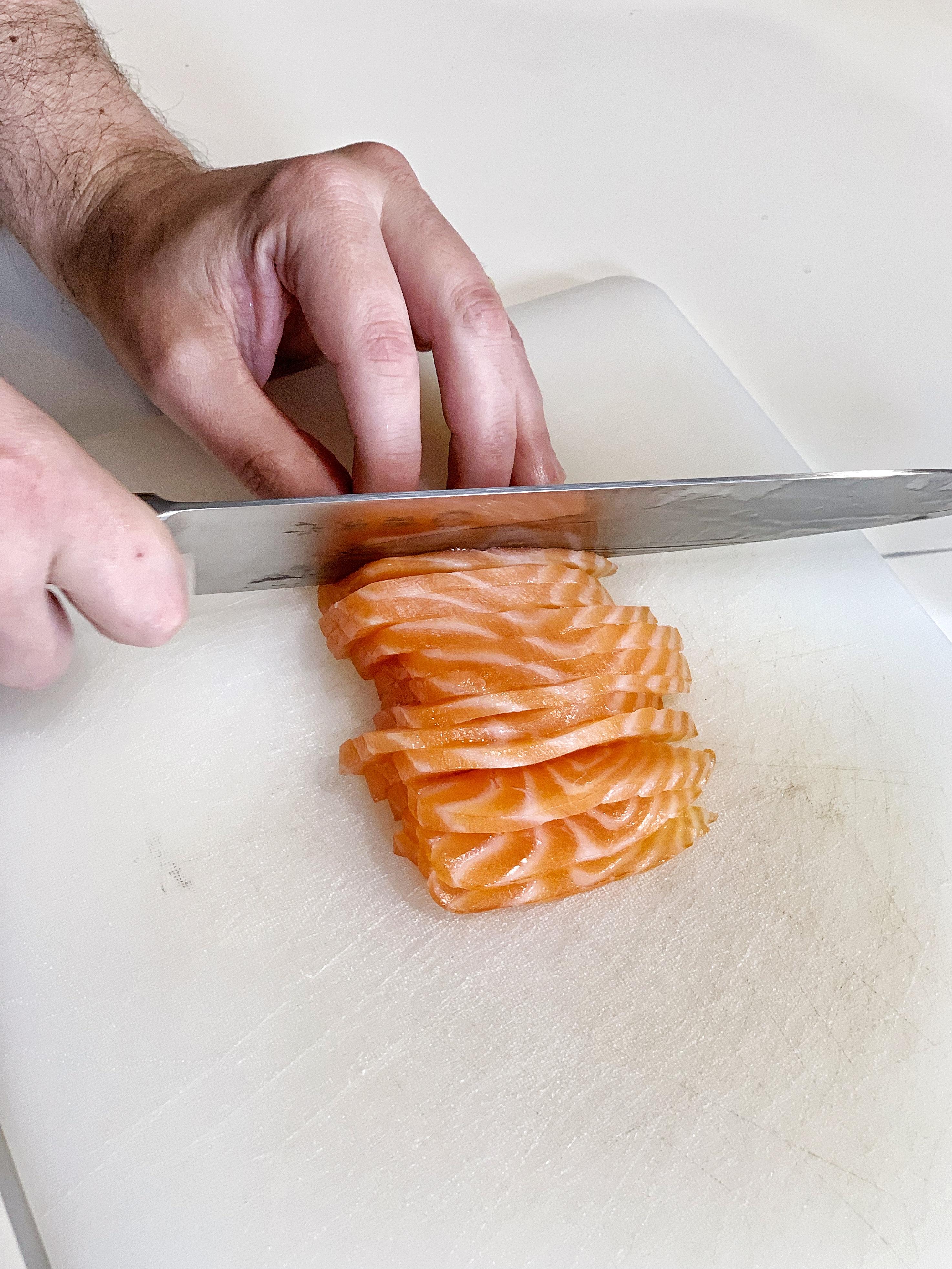 Mano fotografata mentre taglia il salmone