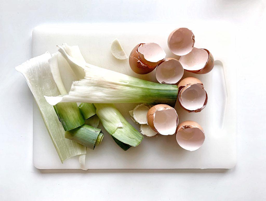 Cipollotti e uova dopo la preparazione delle crepe salata su tagliere bianco