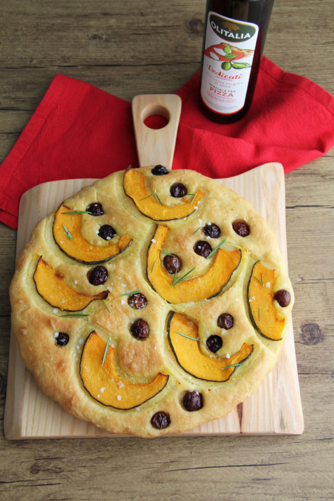 Focaccia-con-Zucca-e-Olive-Nolche-su-tagliere-con-bottiglia-di-olio e tovagliolo rosso