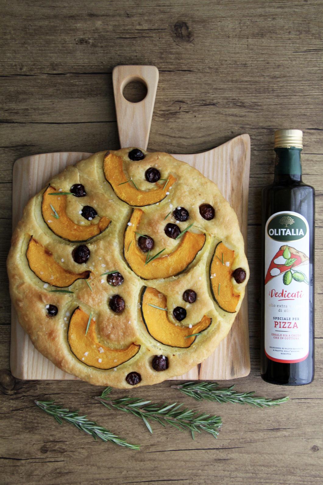 Focaccia con Zucca e Olive Nolche su tagliere con bottiglia di olio e rosmarino su tavolo in legno scuro