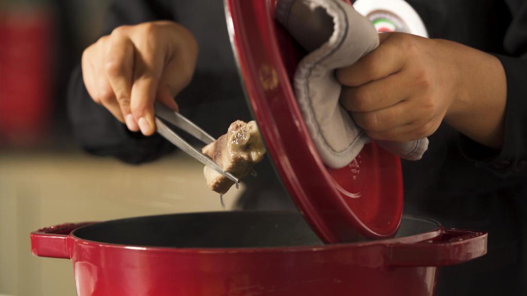 Mani che cucinano con una pentola rossa